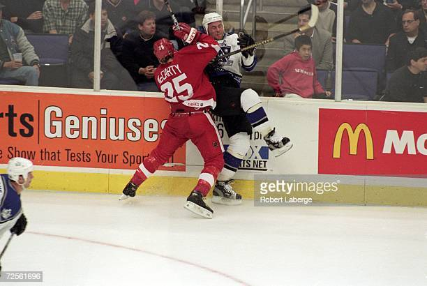 Mattias Norstrom of the Los Angeles Kings is Smashed by Darren McCarty of the Detroit Red Wings during the Western Conference Quarter Finals game at...