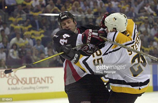 Alexei Zhitnik of the Buffalo Sabres and Kevin Stevens of the Pittsburgh Penguins collide during game three of the Eastern Conference Playoff...