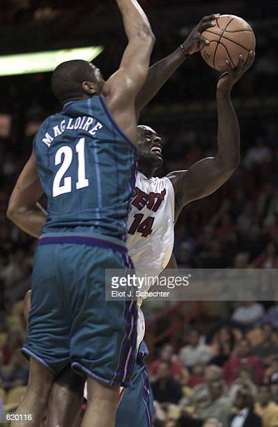 Anthony Mason of the Miami Heat shoots around Jamaal Maglorie of the Charlotte Hornets in the first half at American Airlines Arena in Miami,...
