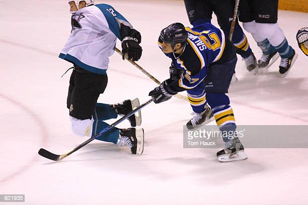 Bryce Salvador of the St Louis Blues trips #Bill Lindsay of the San Jose Sharks during game 4 of the Western Conference Playoff Quarerfinals at the...