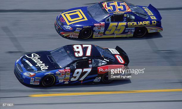 Driver Kurt Busch who drives the Roush Racing Rubbermaid/Sharpie Ford Taurus for Roush Racing races next to car during the Talladega 500 presented by...