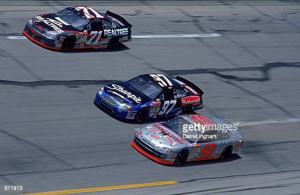 Driver Kurt Busch who drives the Roush Racing Rubbermaid/Sharpie Ford Taurus for Roush Racing races next to car and car during the Talladega 500...