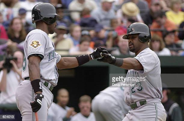 Greg Vaughn right of the Tampa Bay Devil Rays is congratulated by teammate Fred McGriff after Vaughns second home run of the day which gave the Devil...