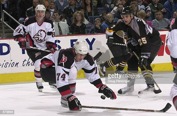 Jay McKee of the Buffalo Sabres knocks down the puck in front of Kevin Stevens of the Pittsburgh Penguins during first period action in game two of...