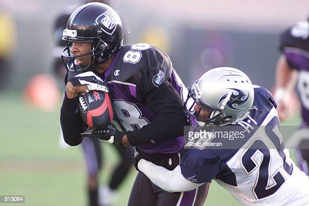 Junior Lord of the Chicago Enforcers fights off the tackle of Dell McGee of the Los Angeles Xtreme at Memorial Coliseum in Los Angeles California...