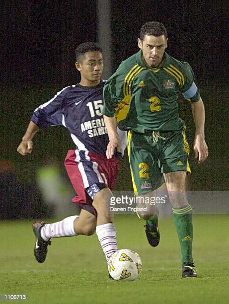 Kevin Muscat of the Australian Socceroos gets past Pati Feagiai of American Samoa during the Oceania group one World Cup qualifier match between...