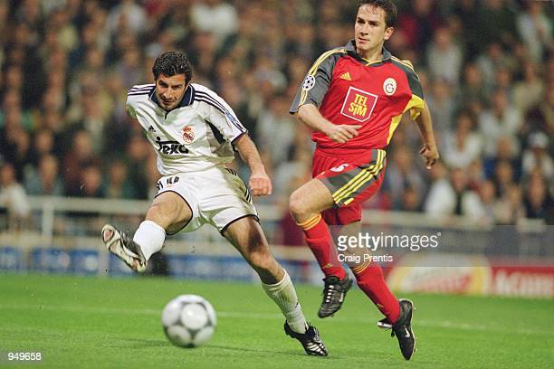Luis Figo of Real Madrid cosses the ball as Emre Asik of Galatasaray closes in during the UEFA Champions League Quarter Finals second leg match...