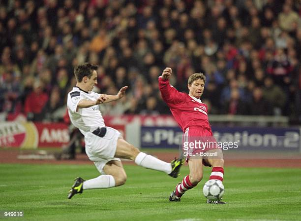 Michael Tarnat of Bayern Munich crosses the ball past Gary Neville of Manchester United to make the opening goal during the UEFA Champions League...