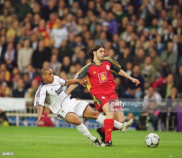 Roberto Carlos of Real Madrid challenges Umit Davala of Galatasaray during the UEFA Champions League Quarter Finals second leg match played at the...
