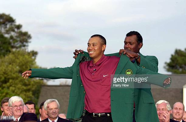 Tiger Woods of the USA is presented with his second green jacket by defending champion Vijay Singh of Fiji after the final day of the 2001 Masters at...