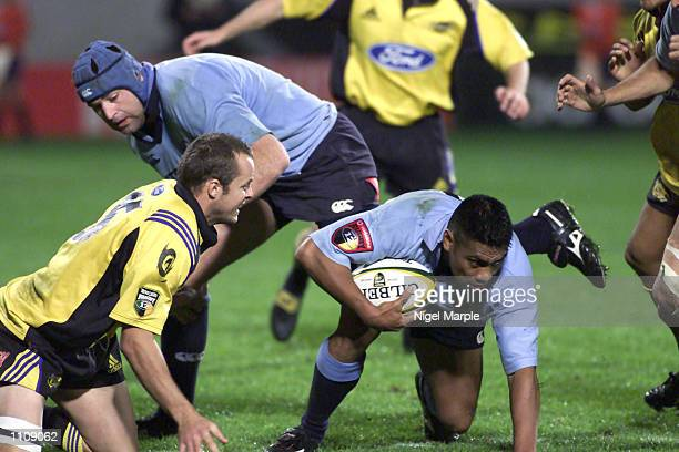 Tui Talaia of the Waratahs tries to slip away from Christian Cullen of the Hurricanes during the Super 12 match between the Hurricanes and the...