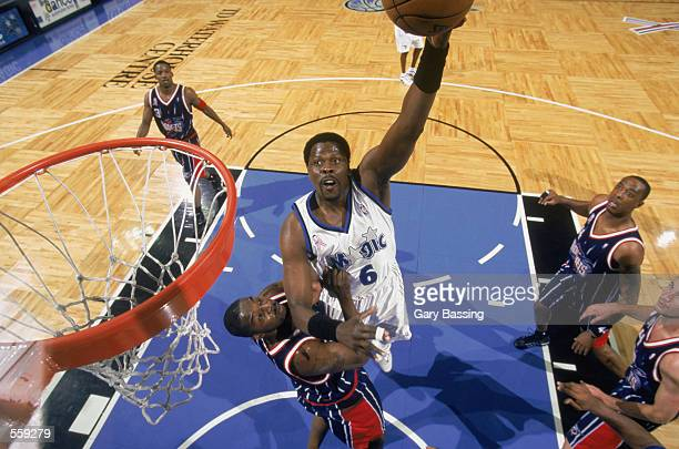 Center Patrick Ewing of the Orlando Magic shoots the ball over guard Walt Williams of the Houston Rockets during the NBA game at the TD Waterhouse in...