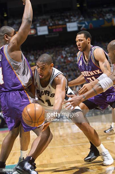 Center Tim Duncan of the San Antonio Spurs passes around forward Alton Ford of the Phoenix Suns during the NBA game at the Alamodome in San Antonio...