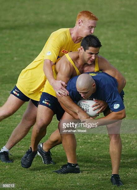 Corey Parker of the Brisbane Broncos is tackled by teamates Brad Meyers and Carl Webb during a team training session held today at the Broncos...