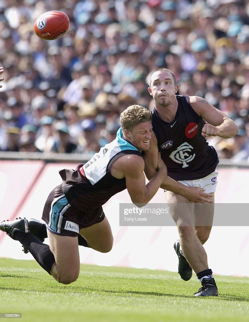 Darren Hulme #27 for Carlton handballs under pressure from Damien Hardwick #11 for Port in the match between Port Power and the Carlton Blues in round 4 of the AFL played at Football Park in Adelaide, Australia. DIGITAL IMAGE Mandatory Credit: Tony Lewis/Getty Images