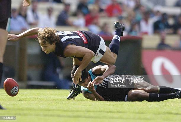 David Gallagher for Carlton tumbles over Che CockatooCollins for Port in the match between Port Power and the Carlton Blues in round 4 of the AFL...