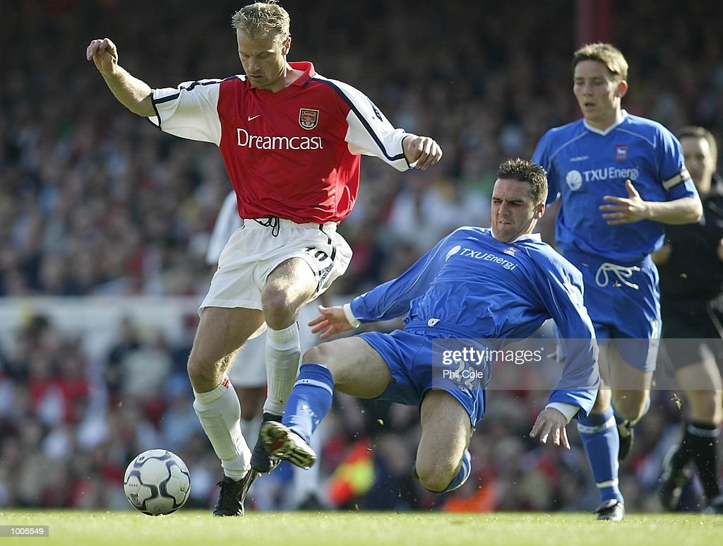 Dennis Bergkamp of Arsenal is tackled by Tommy Miller of Ipswich Town during the FA Barclaycard Premiership match between Arsenal and Ipswich Town at Highbury, London. DIGITAL IMAGE Mandatory Credit: Phil Cole/Getty Images