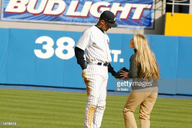 Derek Jeter of the New York Yankees is approached by a fan who run onto the field during the opening day game against the Tampa Bay Devil Rays at...