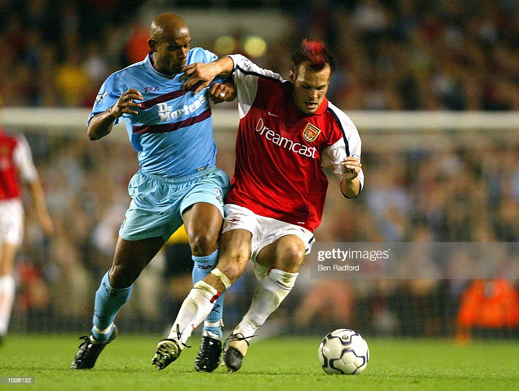 Fredrik Ljungberg of Arsenal holds off the challenge of Trevor Sinclair of West Ham during the FA Barclaycard Premiership match between Arsenal and West Ham United at Highbury, London. DIGITAL IMAGE Mandatory Credit: Ben Radford/Getty Images