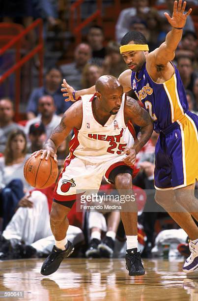 Guard Anthony Carter of the Miami Heat dribbles the ball as guard Derek Fisher of the Los Angeles Lakers play defense during the NBA game at the...