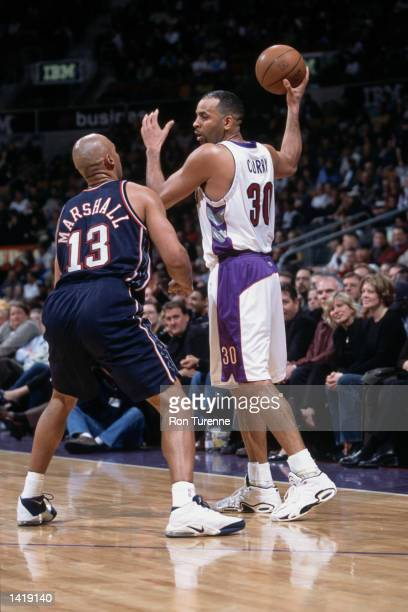 Guard Dell Curry of the Toronto Raptors holds the ball as forward Donny Marshall of the New Jersey Nets plays defense during the NBA game at the Air...