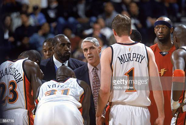 Head coach Brian Winters of the Golden State Warriors talks to three of his players guard Jason Richardson center Adonal Foyle and forward Troy...