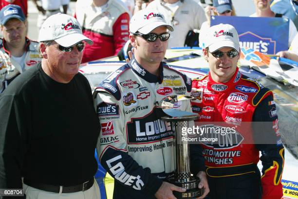 Hendrick Motorsports driver Jimmie Johnson poses withe the winners trophy with co-owners Rick Hendrick and Jeff Gordon in victory lane after winning...