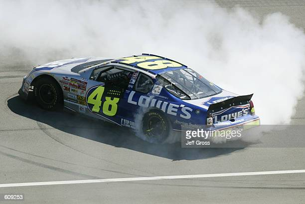 Hendrick Racing driver Jimmie Johnson celebrates by doing donuts on the front stretch after winning the NASCAR Winston Cup Series NAPA Auto Parts 500...
