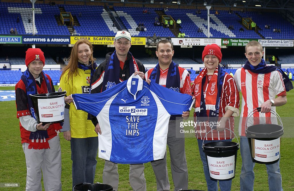 Lincoln City fans who have been collecting funds to help their club financially pose for photographs on the pitch before the Everton v Leicester City FA Barclaycard Premiership match at Goodison Park, Everton. DIGITAL IMAGE Mandatory Credit: Clive Brunskill/Getty Images