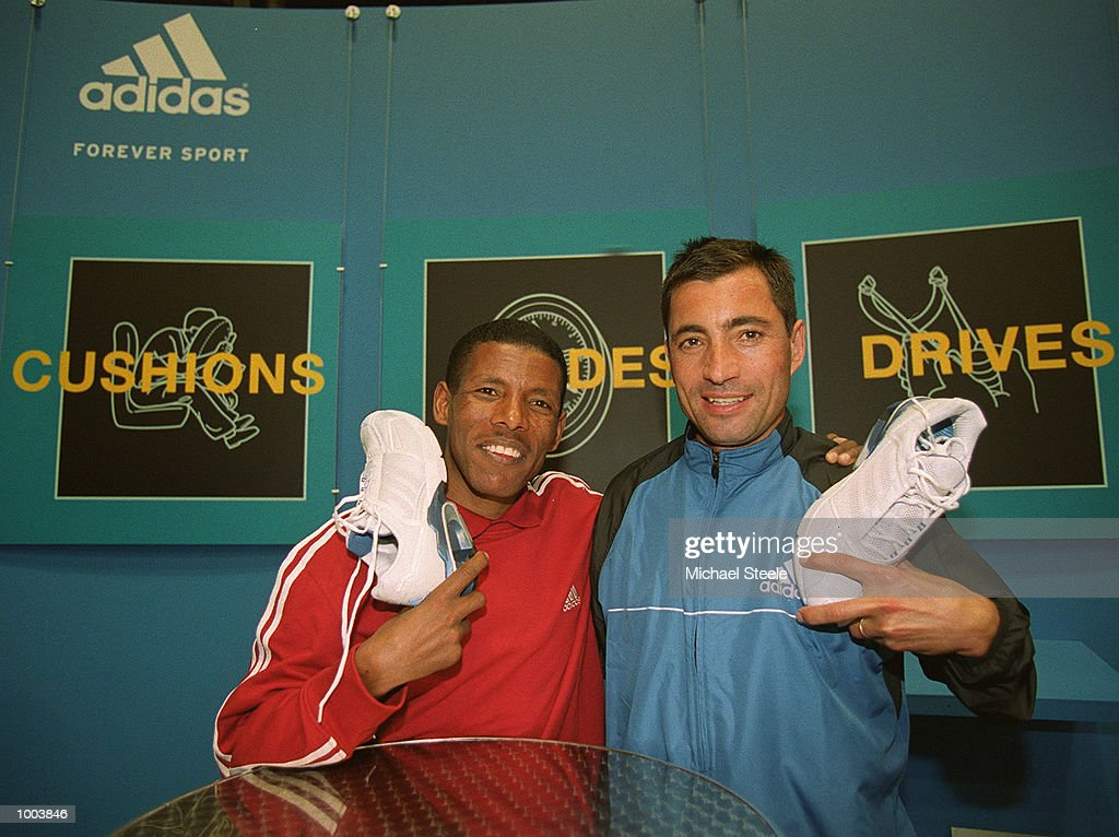 Marathon debutant Haile Gebrselassie (left) of Ethiopia holds his A3 running shoes and poses with 3 time winner Antonio Pinto of Portugal at the adidas stand at the London Marathon Exhibition at the London Arena in Docklands, London. Mandatory Credit: Michael Steele/Getty Images