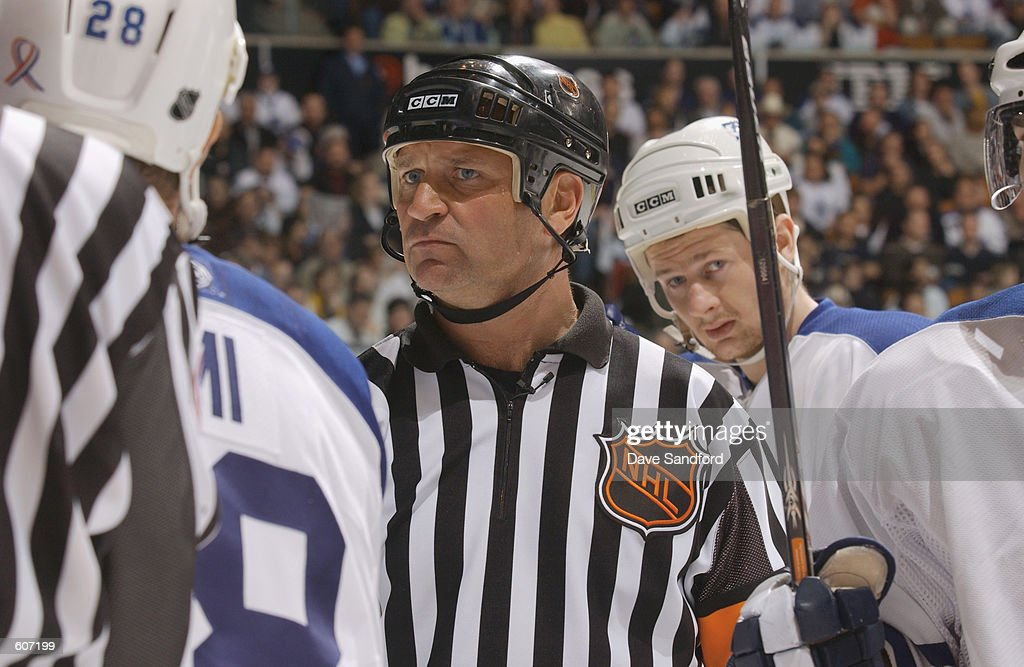 Referee Don Koharski separates players during the game between the New York Islanders and the Toronto Maple Leafs during game two of the Stanley Cup playoffs at the Air Canada Centre in Toronto, Canada. The Leafs won 2-0. DIGITAL IMAGE. Mandatory Credit: Dave Sandford/Getty Images/NHLI