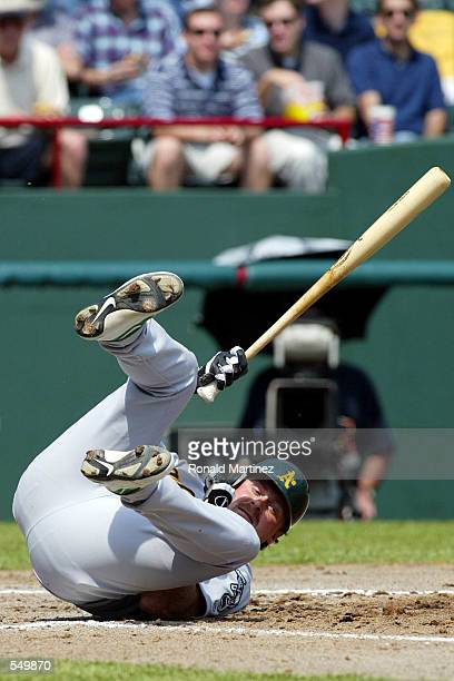 Right fielder Jeremy Giambi of the Oakland Athletics falls over while avoiding an errant pitch against the Texas Rangers at the Ballpark in Arlington...