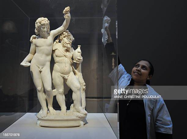 Apres les USA les collections d'art romain du Louvre s'exposent a Arles A woman cleans up a protective glass surrounding a marble statue of Bacchus...
