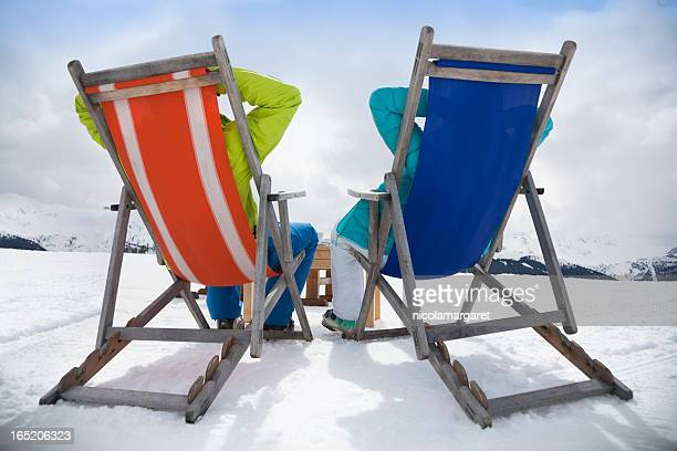 Apres-ski Couple reclining in deckchairs