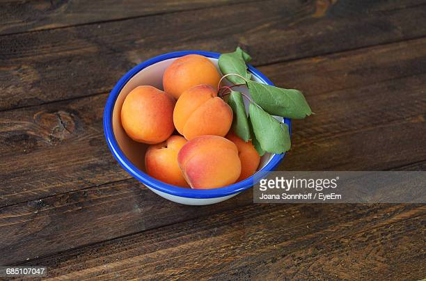 Apricot In Bowl On Wooden Table