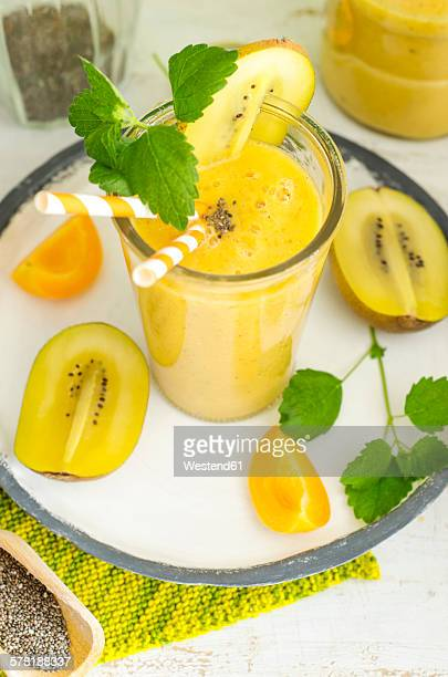 Apricot-kiwi-smoothie with chia seeds and mint in a glass with drinking straw