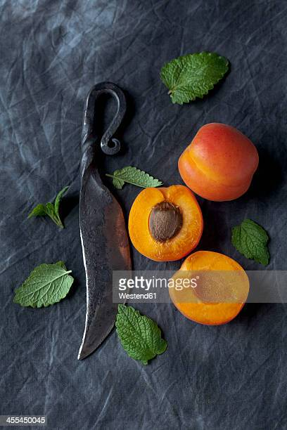 Apricots with leaves and knife on black textile, close up