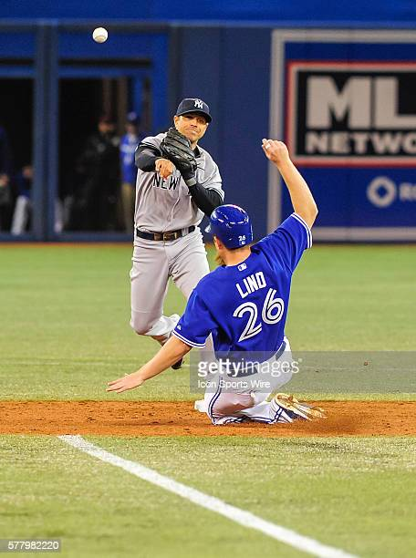New York Yankees infielder Brian Roberts tries to complete a double play with Toronto Blue Jays designated hitter Adam Lind sliding in The Toronto...