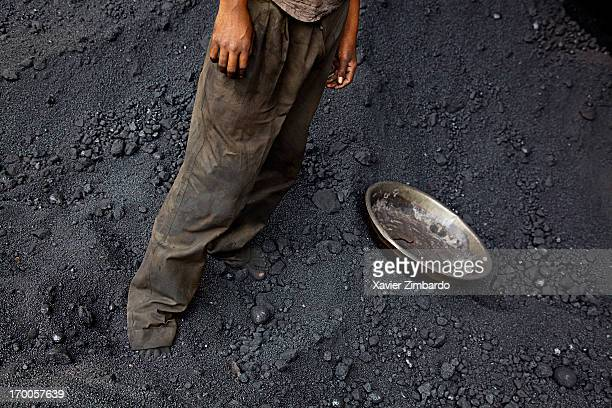 A worker at work stands in a pile of coal on April 05 2009 in a fabric dyeing factory in Rajasthan India The pan lying close by is used to collect...