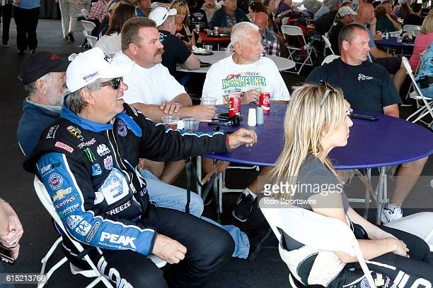 John Force and Brittany Force sit with fans while waiting to speak during a driver appearance in the Club Nitro hospitality tent during the DENSO...