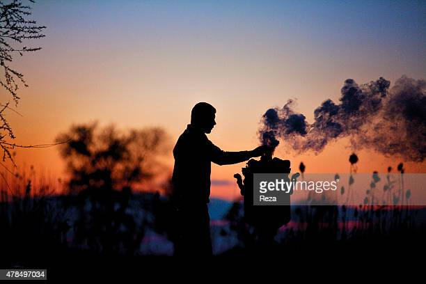 April 1 Tea House the road from Baku to Ganja Azerbaijan A tea house at a rest stop on the road from Baku to Ganja at dusk A man simmers tea on a...