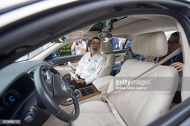 CHONGQING April 12 2016 A technician introduces selfdriving techniques to journalists during the departure ceremony of a 2000kilometer road test of...