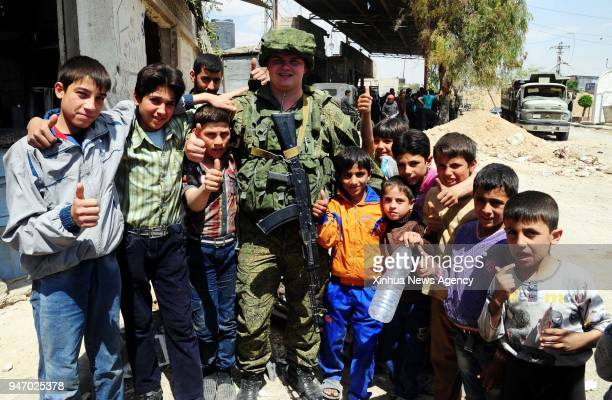 DAMASCUS April 15 2018 A Russian military policeman poses with children in the Douma district of Damascus Syria on April 15 2018 On Saturday the...