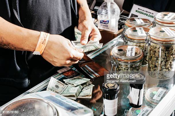 A customer counts out money to pay for his marijuana purchase in Tru Cannabis marijuana dispensary in Denver Colorado on April 19 2015 In late...