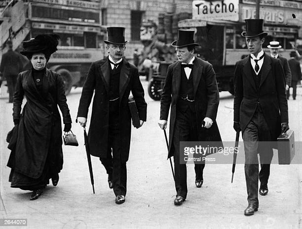 Winston Churchill listens attentively to David Lloyd George Chancellor of the Exchequer while walking in Central London with him his wife and his...
