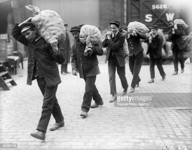 London and South West railwaymen carrying sacks of potatoes to be planted on railway waste ground