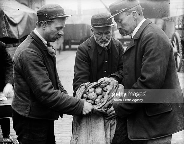London and South West railwaymen inspecting a sack of potatoes to be planted on railway waste ground