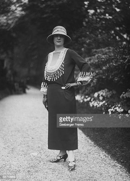 Ankle length dress by the couturier Charles Frederick Worth decorated with an intricately beaded yoke and cuffs The model is also wearing leather...
