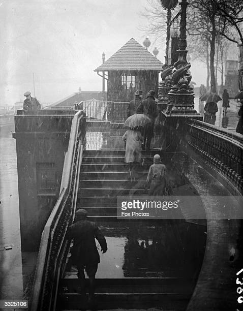 Commuters walking up to Embankment bridge in London whilst sleet is falling