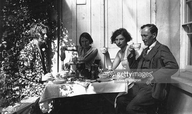 From left to right Pansy Lamb Vivien John Poppet John and Henry Lamb having tea outofdoors at Ham Spray Vivien and Poppet are daughters of painter...